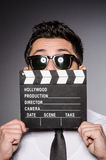 Young caucasian man with clapperboard against gray Stock Image
