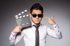 Young caucasian man with clapperboard against gray Royalty Free Stock Photos