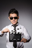 Young caucasian man with clapperboard against gray Stock Photo