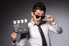 Young caucasian man with clapperboard against gray Stock Photography