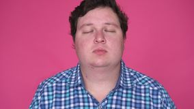 Young Caucasian man with closed eyes. Studio portrait over pink wall background.  stock video