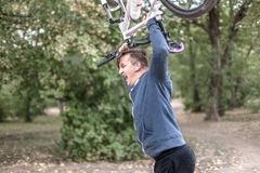 Young caucasian man crashes his bicycle down with emotions royalty free stock image