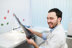 Young caucasian man doctor examines MRI image of human head in office looking at the patient and smiling