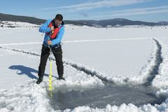Young Caucasian man drilling the ice on a frozen lake with ice auger drill. Selective focus stock image