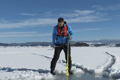 Young Caucasian man drilling ice on a frozen lake with yellow ice auger drill wearing life vest. Selective focus. Young Caucasian man drilling ice on a frozen royalty free stock images