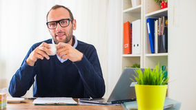 A young caucasian man drinking coffee in his office. Royalty Free Stock Photo