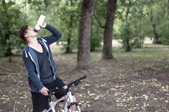Young caucasian man drinks the water bicycling in the park stock photos