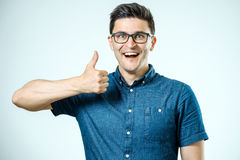 Young caucasian man with glasses showing thumbs up Royalty Free Stock Photo
