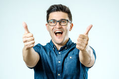 Young caucasian man with glasses showing thumbs up Royalty Free Stock Image