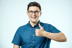 Young caucasian man with glasses showing thumbs up Royalty Free Stock Photos