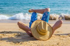 Young male tourist sunbathing on beach at sea. Young caucasian man with hat lying on beach at sea Royalty Free Stock Images
