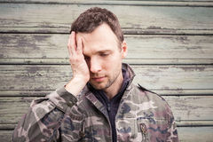 Young Caucasian man with headache in camouflage Stock Image