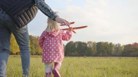 Young caucasian man helping his adorable little daughter playing with a pink toy airplane. Pretty blonde smiling girl in stock video footage