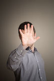 Young Caucasian man hiding face with hand Royalty Free Stock Photography