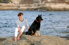 Young Caucasian Man and His Dog. Sit on the rock in the Black sea at sunset Royalty Free Stock Image
