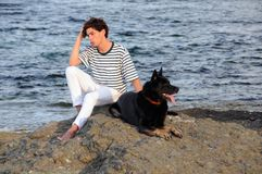 Young Caucasian Man and His Dog. Sit on the rock in the Black sea at sunset Royalty Free Stock Photography