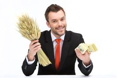 Young caucasian man holding fresh wheat and dollars. Royalty Free Stock Photo