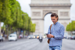 Young caucasian man holding a phone on the Champs Royalty Free Stock Photo
