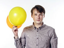 Young caucasian man holding yellow air balloons in his hand Stock Photo