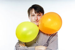 Young caucasian man holding yellow air balloons in his hand Royalty Free Stock Photo