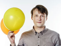Young caucasian man holding yellow air balloons in his hand Royalty Free Stock Image