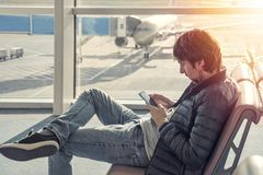 Young caucasian man in jeans and jacket sitting in airport waiting lounge hall, using mobile phone. stock photo