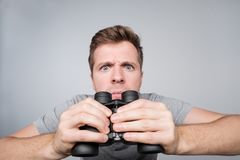 Young caucasian man looking with binocular ahead trying to see some important details. He saw his wife with lover and is very angry now royalty free stock image