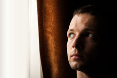 Young Caucasian man looking in bright window Stock Photography