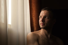 Young Caucasian man looks in bright window Royalty Free Stock Images