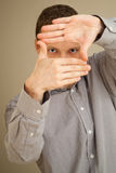 Young Caucasian man looks through hands frame, casual studio por Royalty Free Stock Photo