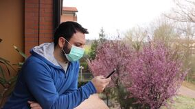 Young caucasian man with mask looking out onto home terrace during quarantine due to coronavirus covid19 pandemic