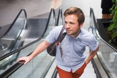 Young caucasian man moving up on an escalator at the airport. Travelling with backpacker Stock Photos