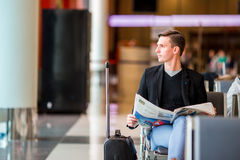 Young caucasian man with newspaper at the airport while waiting for boarding. Casual young businessman wearing suit Stock Image