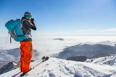 Young caucasian man photographer talking pictures while backcoun. Try skiing on a beautiful sunny day with fresh snow Royalty Free Stock Photo