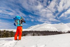 Young caucasian man photographer talking pictures while backcoun. Try skiing on a beautiful sunny day with fresh snow Stock Images