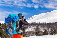 Young caucasian man photographer talking pictures while backcoun. Bla bla Young caucasian man photographer talking pictures while backcountry skiing on a Stock Images