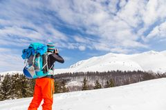 Young caucasian man photographer talking pictures while backcoun. Try skiing on a beautiful sunny day with fresh snow Royalty Free Stock Images