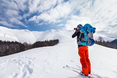 Young caucasian man photographer talking pictures while backcoun. Try skiing on a beautiful sunny day with fresh snow Royalty Free Stock Photos