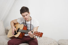 Young Caucasian man playing guitar while sitting on fur sofa Royalty Free Stock Images