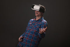 Young Caucasian man playing guitar with virtual reality headset. Man wearing virtual reality glasses,studio shot royalty free stock photography