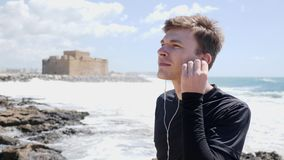 Young caucasian man puts the headphones on standing on the rocky beach with the castle on the background. Slow motion stock footage