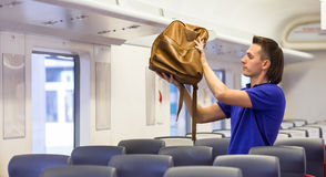 Young caucasian man putting luggage on the top Stock Images