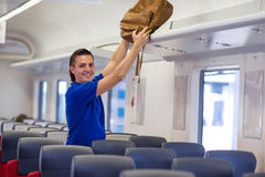 Young caucasian man putting luggage on the top Stock Image