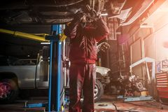 Young caucasian man in red work clothing repairing car royalty free stock images
