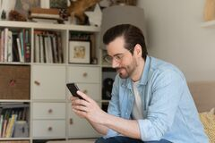 Young man relax at home browsing modern cellphone