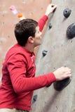 Rock climbing indoors. Young caucasian man rock climbing indoors Stock Photo