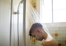 Young caucasian man showering in bathroom Stock Photo