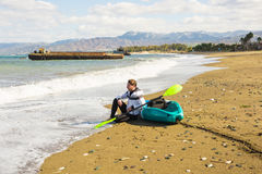 Young caucasian man sitting on beach with kayak Stock Images