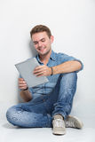 Young caucasian man sitting on the floor holding a tablet pc Stock Images