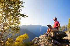 Young caucasian man sitting outdoor on a rock working on a lapto Stock Photography